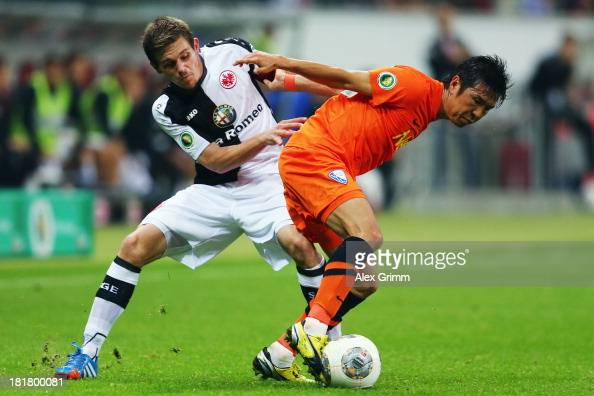 Yusuke Tasaka of Bochum is challenged by Sebastian Jung of Frankfurt during the DFB Cup second round match between Eintracht Frankfurt and VfL Bochum...