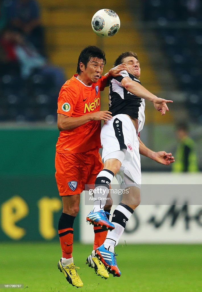 Yusuke Tasaka (L) of Bochum jumps for a header with Sebastian Jung of Frankfurt during the DFB Cup second round match between Eintracht Frankfurt and VfL Bochum at Commerzbank-Arena on September 25, 2013 in Frankfurt am Main, Germany.