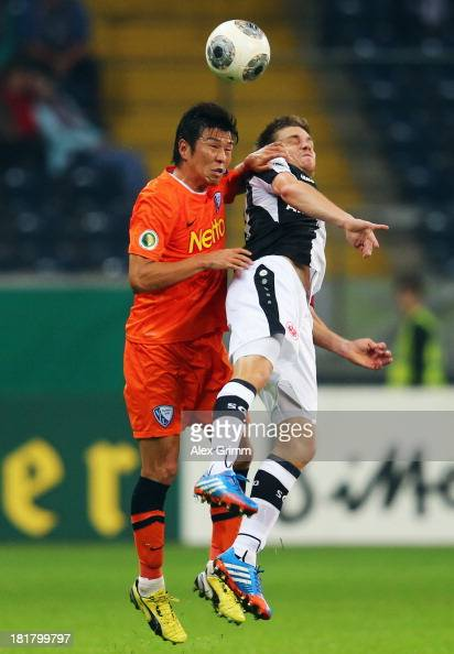 Yusuke Tasaka of Bochum jumps for a header with Sebastian Jung of Frankfurt during the DFB Cup second round match between Eintracht Frankfurt and VfL...