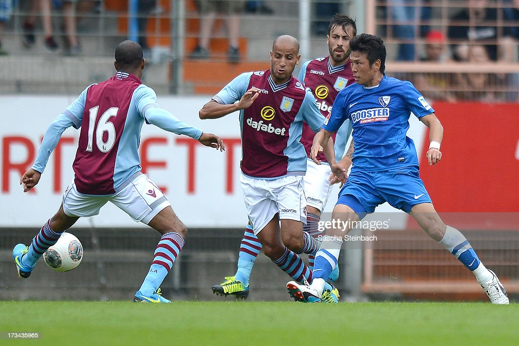 Yusuke Tasaka (R) of Bochum passes the ball during the pre-season friendly match between VfL Bochum and Aston Villa at Rewirpower Stadium on July 14, 2013 in Bochum, Germany.