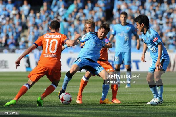 Yusuke Tasaka of Kawasaki Frontale controls the ball under pressure of Kei Koizumi and Thiago Galhardo of Albirex Niigata during the JLeague J1 match...