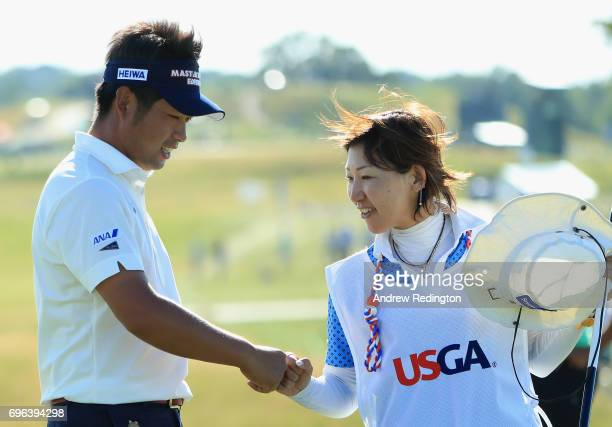 Yuta Ikeda of Japan and caddie Magumi Sakai celebrate after making a birdie on the 18th green during the first round of the 2017 US Open at Erin...