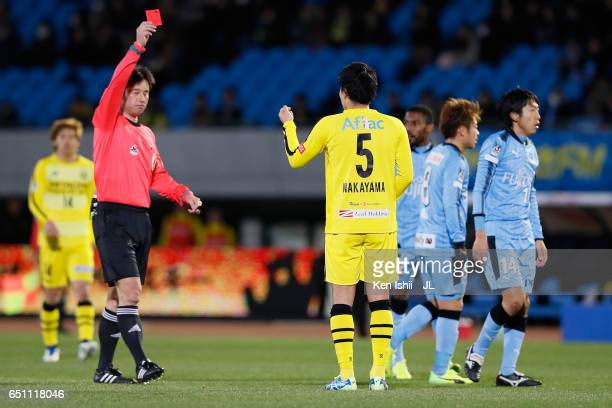 Yuta Nakayama of Kashiwa Reysol is shown a red card by referee Yoshiro Imamura after fouling on Kengo Nakamura of Kawasaki Frontale during the...