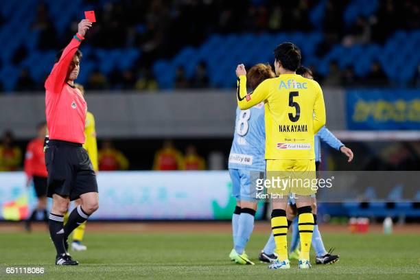 Yuta Nakayama of Kashiwa Reysol is shown a red card by referee Yoshiro Imamura after fouling on Kengo Nakamura of Kawasaki Frontale during the...
