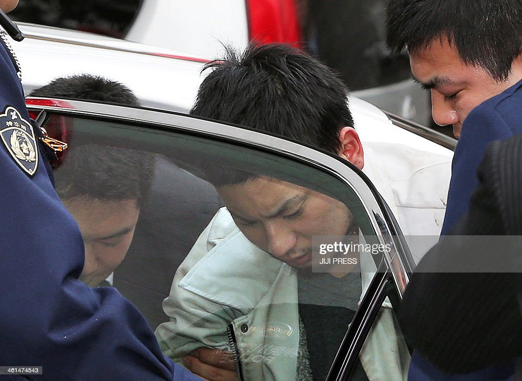 Yuta Sugimoto (C), who slipped away from his guard during a visit to prosecutors in an office building on January 7, arrives at the prosecutors office in Kawasaki, suburban Tokyo on January 9, 2014 after he was arrested in Yokohama, near Kawasaki. Sugimoto had been on the run since january 7 after fleeing during a break in questioning over the gang rape and robbery of a young woman in the city on January 2. AFP PHOTO / JIJI PRESS JAPAN OUT