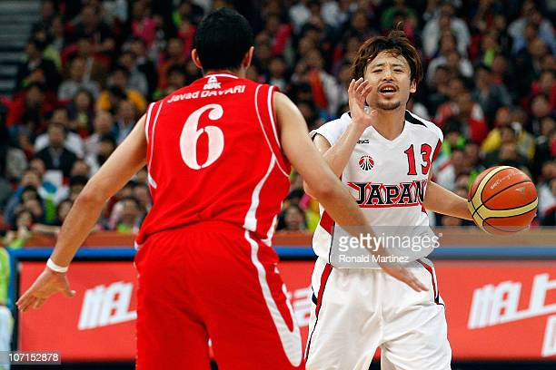 Yuta Tabuse of Japan calls out a play as he is guarded by Javad Davari of Iran during the men's bronze medal basketball game at the Guangzhou...