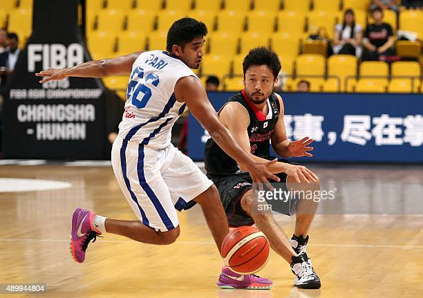 Yuta Tabuse of Japan is challenged by Akilan Pari of India during the FIBA Asia Basketball championship in Changsha China's Hunan province on...
