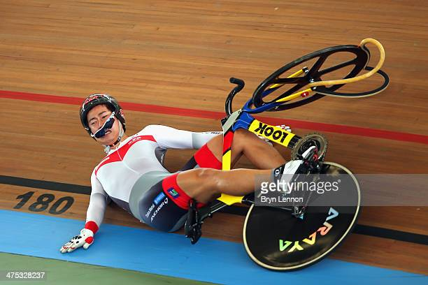 Yuta Wakimoto of Japan slides down the track after crashing during his heat of the Men's Keirin on day two of the 2014 UCI Track Cycling World...