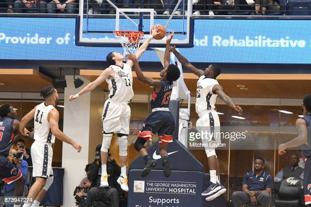 Yuta Watanabe of the George Washington Colonials blocks the shot of Charles Williams of the Howard Bison during a college basketball game at the...