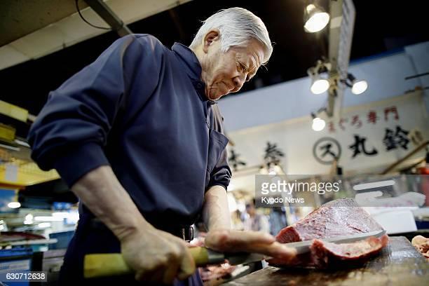 Yutaka Kadono an 80yearold tuna trader at Tokyo's Tsukiji fish market cuts the fish on June 7 2016 At the time Kadono who had been working at the...