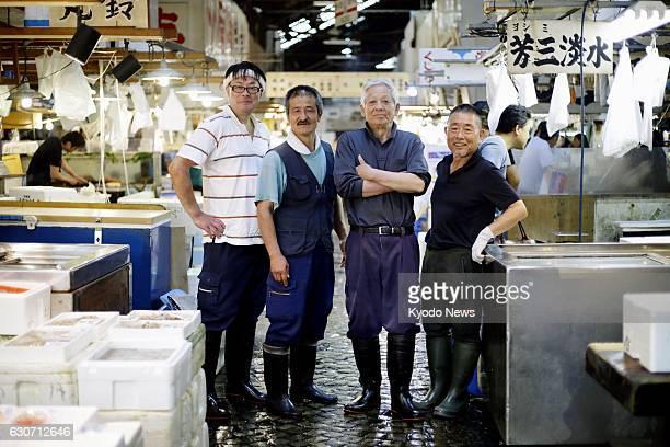Yutaka Kadono an 80yearold tuna trader at Tokyo's Tsukiji fish market poses with employees of his company on June 7 2016 At the time Kadono who had...