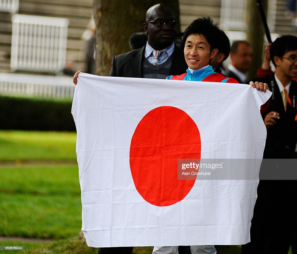 Yutaka Take poses with the Japanese flag at Longchamp racecourse on September 15, 2013 in Paris, France.