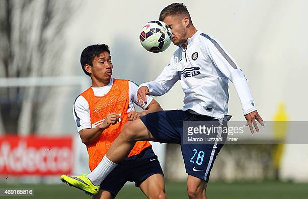 Yuto Nagatomo competes with George Puscas during FC Internazionale training session at the club's training ground on April 10 2015 in Appiano Gentile...