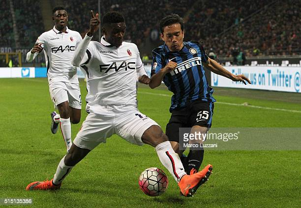 Yuto Nagatomo of FC Internazionale Milano is challenged by Ibrahima M Baye of Bologna FC during the Serie A match between FC Internazionale Milano...