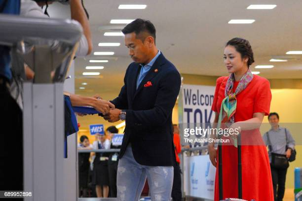 Yuto Nagatomo of Internazionale Milano signs autographs for fans while his wife Airi Taira watches on arrival at Narita International Airport on May...