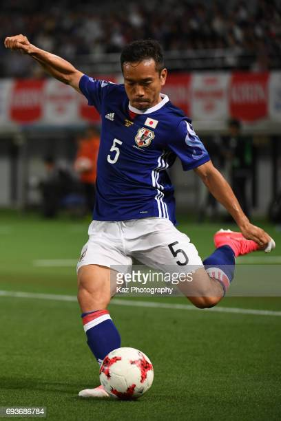 Yuto Nagatomo of Japan crosses the ball under the pressure from Omro Al Midani of Syria during the international friendly match between Japan and...