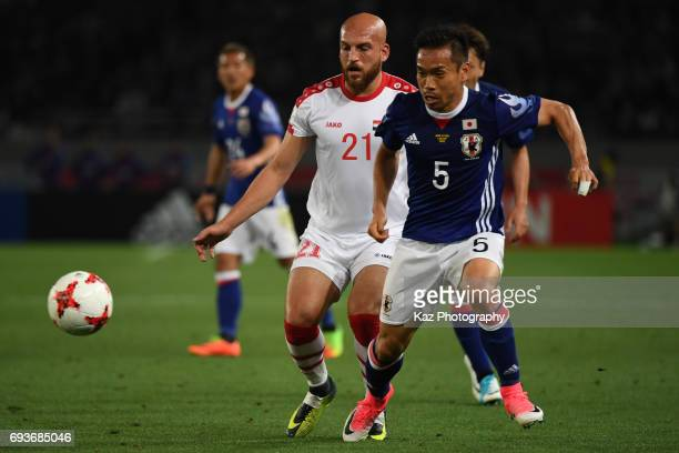 Yuto Nagatomo of Japan dribbles the ball under the pressure from Nassouh Nakkdahli of Syria during the international friendly match between Japan and...