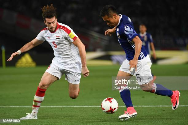 Yuto Nagatomo of Japan dribbles the ball under the pressure from Omro Al Midani of Syria during the international friendly match between Japan and...