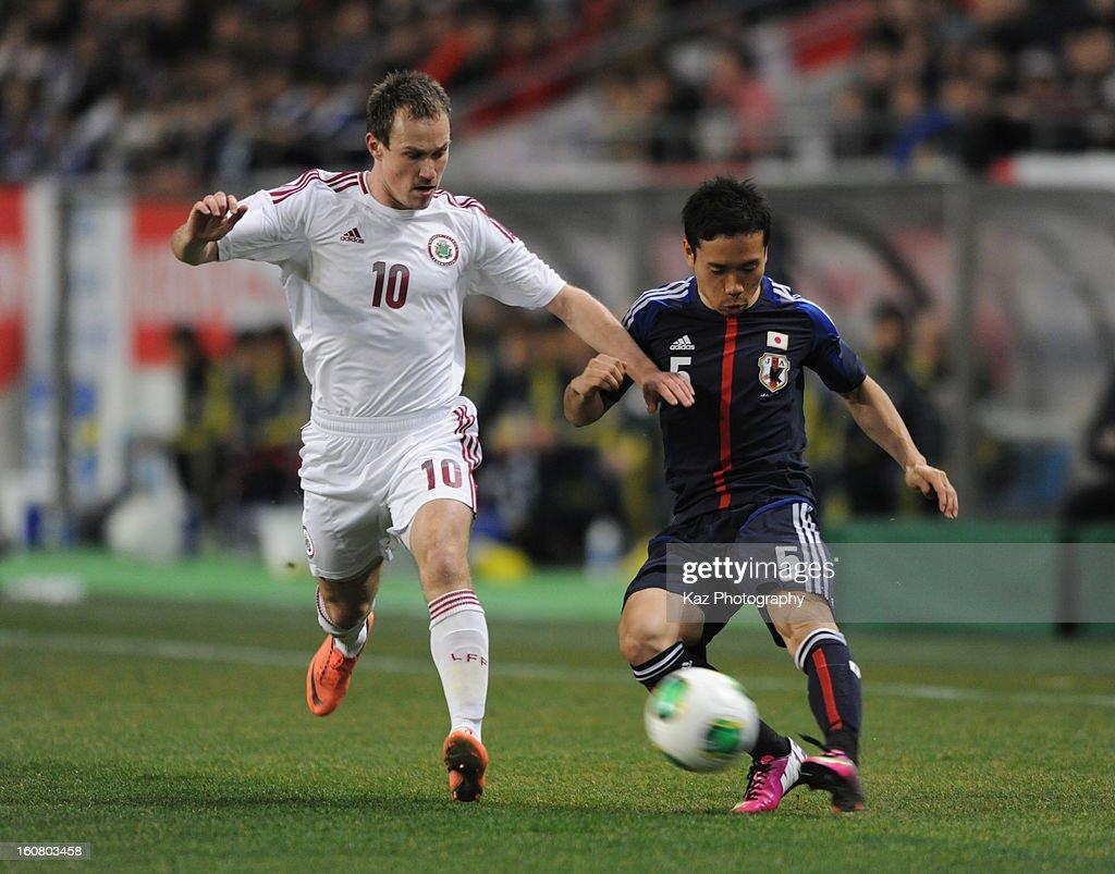 Yuto Nagatomo of Japan sends the cross while Aleksejs Visnakovs of Latovia defends during the international friendly match between Japan and Latvia at Home's Stadium Kobe on February 6, 2013 in Kobe, Japan.
