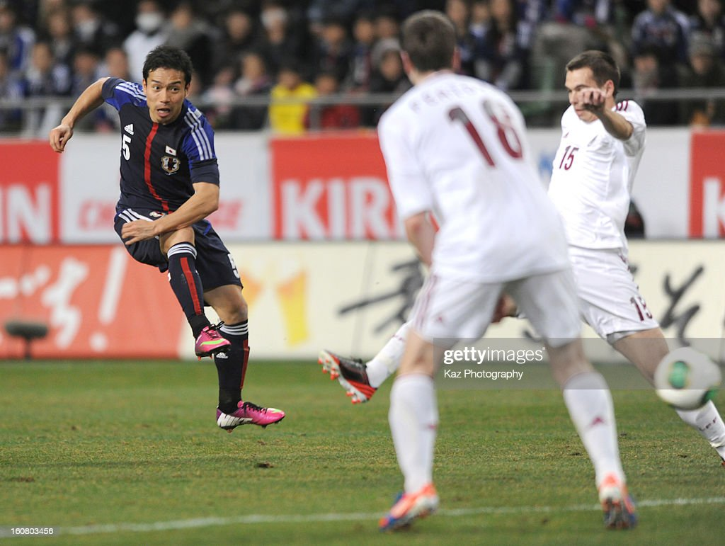 Yuto Nagatomo of Japan shoots the ball while Artus Zjuzins of Latvia challenges during the international friendly match between Japan and Latvia at Home's Stadium Kobe on February 6, 2013 in Kobe, Japan.
