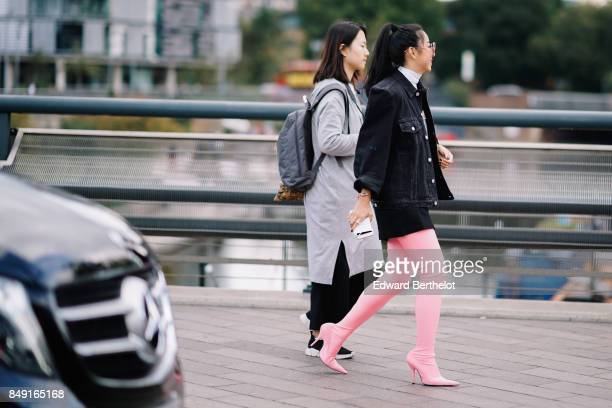 Yuwei Zhangzou wears a black denim jacket pink thigh high leather boots outside Versus during London Fashion Week September 2017 on September 17 2017...