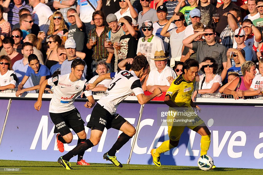 Yuya Kubo (R) of BSC Young Boys vies with Sandro Burki (C) of FC Aarau during the Swiss Super League match between FC Aarau v BSC Young Boys at Brugglifeld on August 10, 2013 in Aarau, Switzerland.