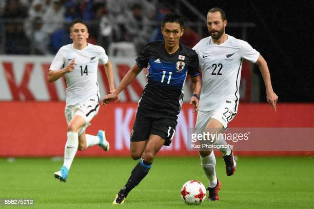 Yuya Kubo of Japan and Andrew Durante of New Zealand compete for the ball during the international friendly match between Japan and New Zealand at...