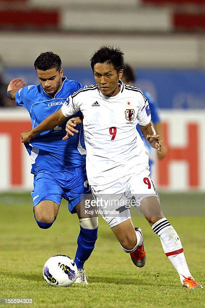 Yuya Kubo of Japan and S Altourki of Kuwait compete for the ball during the AFC U19 Championship Group A match between Kuwait and Japan at Emirates...