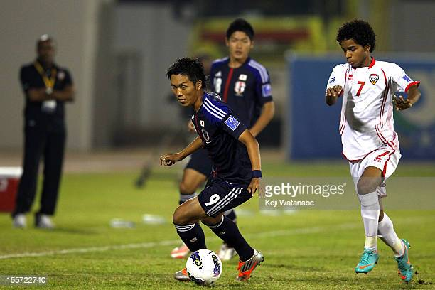 Yuya Kubo of Japan and W Ambar of UAE compete for the ball during the AFC U19 Championship Group A match between the United Arab Emirates and Japan...