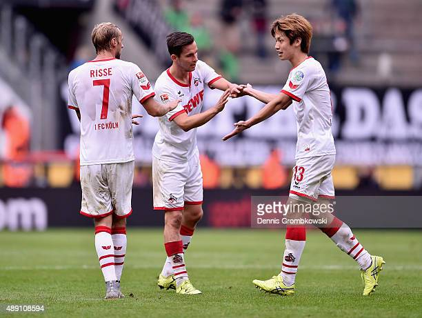 Yuya Osako of 1 FC Koeln high fives with team mates Pawel Olkowski and Marcel Risse during the Bundesliga match between 1 FC Koeln and Borussia...