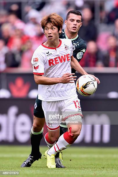 Yuya Osako of 1 FC Koeln is challenged by Granit Xhaka of Borussia Moenchengladbach during the Bundesliga match between 1 FC Koeln and Borussia...