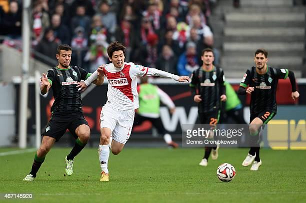 Yuya Osako of 1 FC Koeln is challenged by Santiago Garcia of SV Werder Bremen during the Bundesliga match between 1 FC Koeln and SV Werder Bremen at...