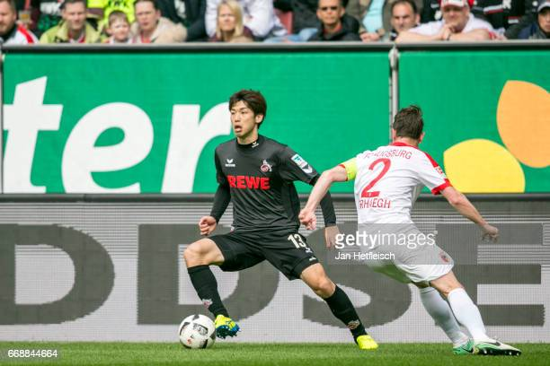 Yuya Osako of Cologne and Paul Verhaegh of FC Augsburg battle for the ball during the Bundesliga match between FC Augsburg and 1 FC Koeln at WWK...