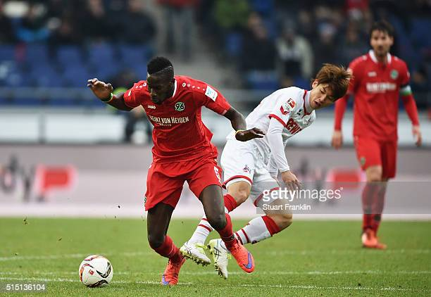 Yuya Osako of Cologne is challenged by Salif Sané of Hannover during the Bundesliga match between Hannover 96 and 1 FC Koeln at HDIArena on March 12...