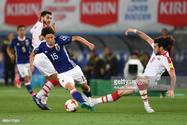 Yuya Osako of Japan and Al Midani Omro of Syria compete for the ball during the international friendly match between Japan and Syria at Tokyo Stadium...