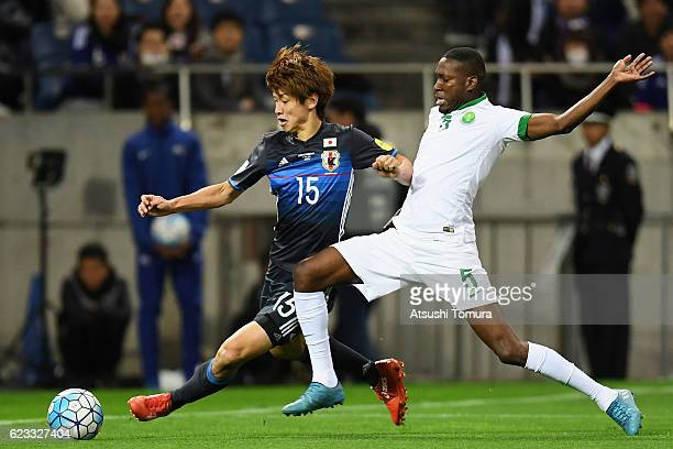 Yuya Osako of Japan and Omar Ibrahim Othman of Saudi Arabia compete for the ball during the 2018 FIFA World Cup Qualifier match between Japan and...