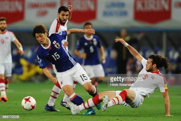 Yuya Osako of Japan and Omoro Al Midani of Syria compete for the ball during the international friendly match between Japan and Syria at Tokyo...