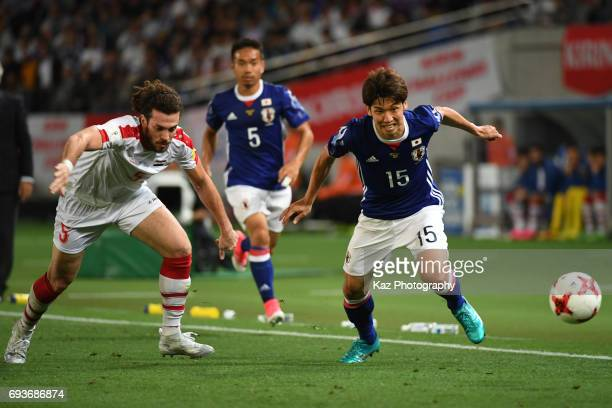 Yuya Osako of Japan and Omro Al Midani of Syria compete for the ball during the international friendly match between Japan and Syria at Tokyo Stadium...