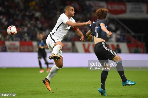 Yuya Osako of Japan and Winston Reid of New Zealand compete for the ball during the international friendly match between Japan and New Zealand at...