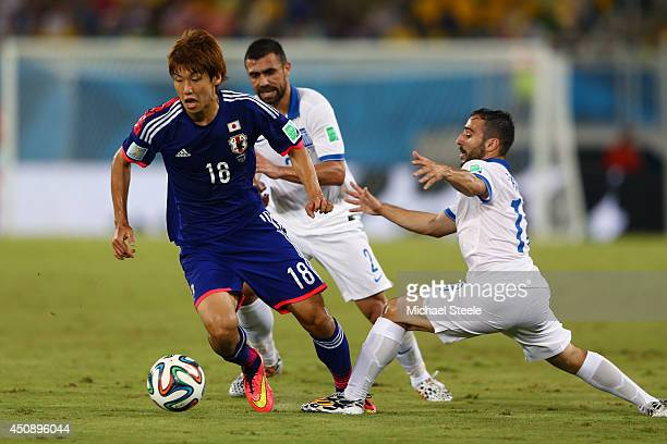 Yuya Osako of Japan controls the ball against Giannis Fetfatzidis of Greece during the 2014 FIFA World Cup Brazil Group C match between Japan and...