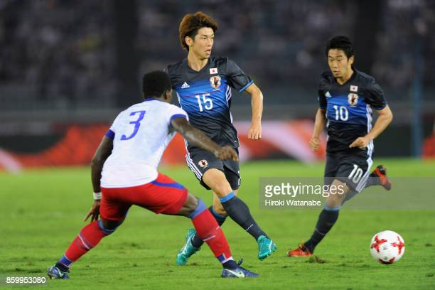 Yuya Osako of Japan takes on Mechack Jerome of Haiti during the international friendly match between Japan and Haiti at Nissan Stadium on October 10...
