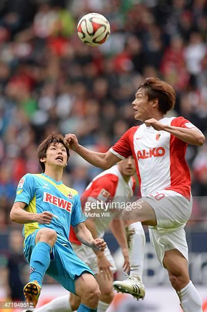 Yuya Osako of Koeln and JeongHo Hong of Augsburg jump for a header during the Bundesliga match between FC Augsburg and 1 FC Koeln at SGL Arena on May...