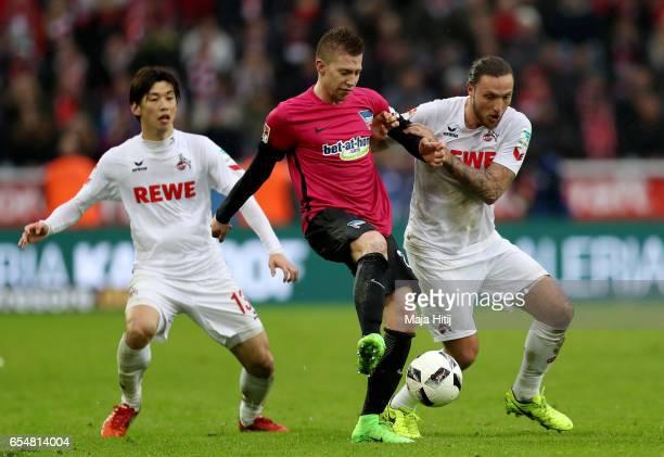 Yuya Osako of Koeln and Marko Hoeger of Koeln challenges Mitchell Weiser of Berlin during the Bundesliga match between 1 FC Koeln and Hertha BSC at...