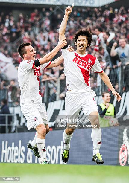 Yuya Osako of Koeln celebrates his team's third goal with team mate Slawomir Peszko during the Bundesliga match between 1 FC Koeln and Eintracht...