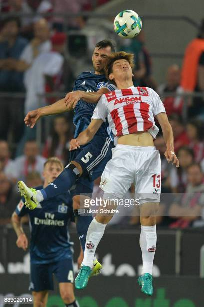 Yuya Osako of Koeln fight for the ball with Mergim Mavraj of Hamburg during the Bundesliga match between 1 FC Koeln and Hamburger SV at...