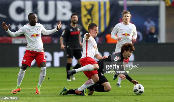 Yuya Osako of Koeln is challenged by Diego Demme of Leipzig during the Bundesliga match between RB Leipzig and 1 FC Koeln at Red Bull Arena on...