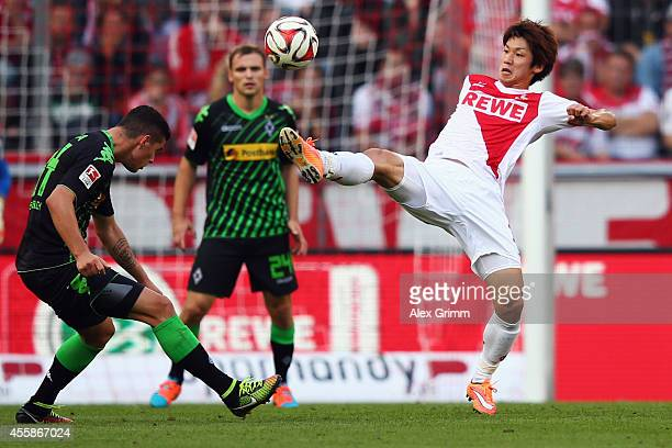 Yuya Osako of Koeln is challenged by Granit Xhaka of Moenchengladbach during the Bundesliga match between 1 FC Koeln and Borussia Moenchengladbach at...