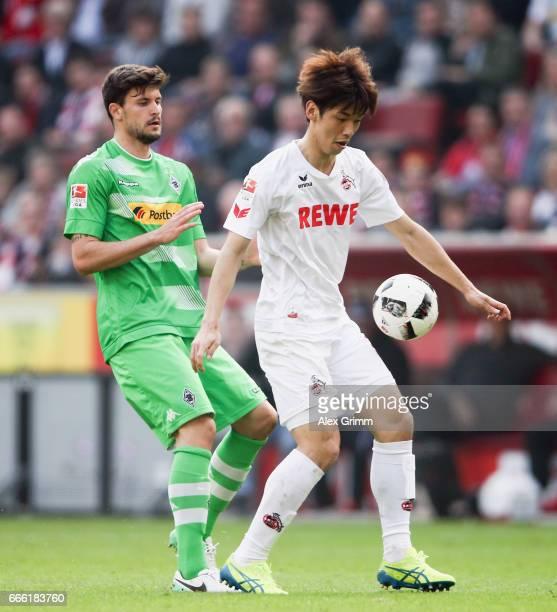 Yuya Osako of Koeln is challenged by Tobias Strobl of Moenchengladbach during the Bundesliga match between 1 FC Koeln and Borussia Moenchengladbach...