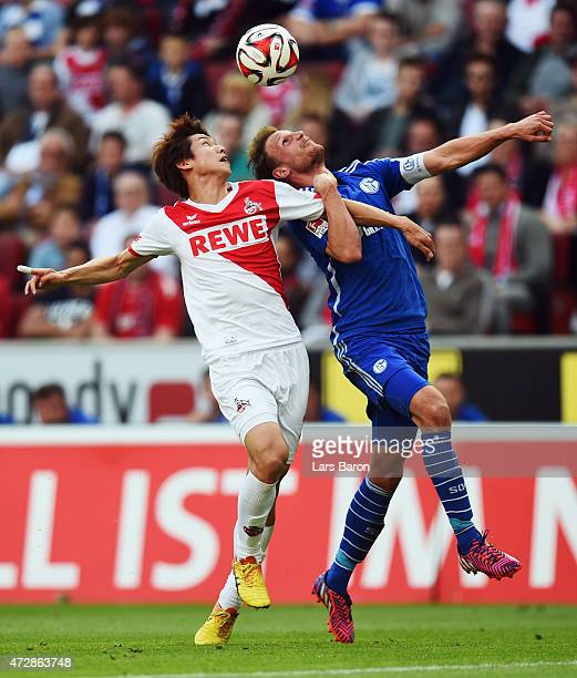 Yuya Osako of Koeln jumps for a header with Benedikt Hoewedes of Schalke during the Bundesliga match between 1 FC Koeln and FC Schalke 04 at...