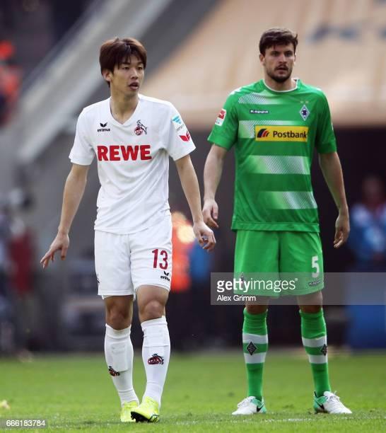 Yuya Osako of Koeln stands next to Tobias Strobl of Moenchengladbach during the Bundesliga match between 1 FC Koeln and Borussia Moenchengladbach at...